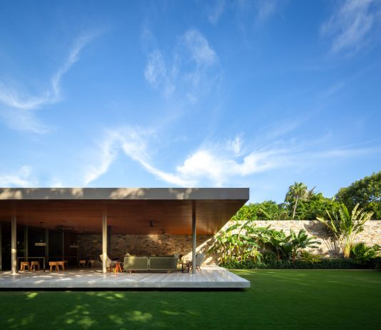 The stone wall divides the house into two programmatic volumes: The social area in the glass box that opens onto the garden/pool and the private area in the wooden volume.