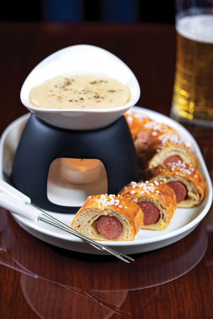 Pigs in a pretzel dough blanket served with warm pilsner cheese fondue, populate Henry's menu.
